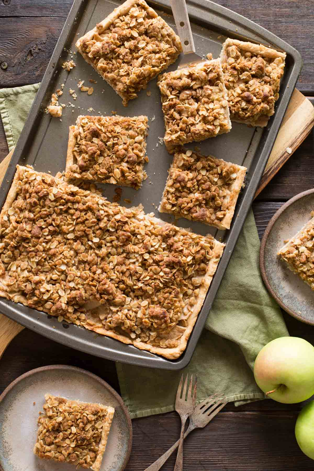 A top down view of a Dutch Apple Slab Pie with a few pieces cut out and fresh apples scattered around.