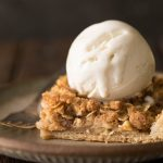 A close up view a piece of Dutch Apple Slab Pie with a scoop of vanilla ice cream on top.