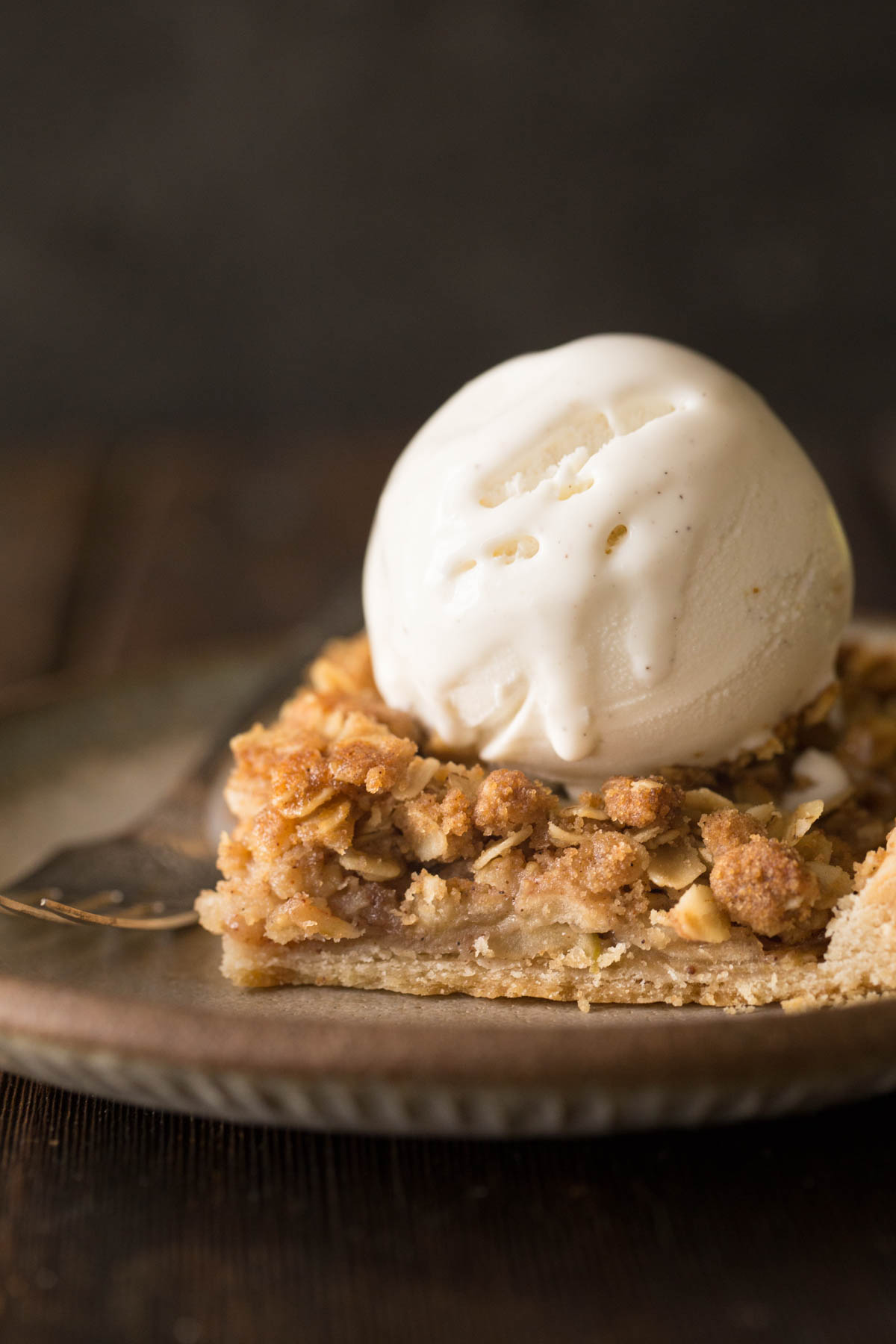 A close up view of a square of Dutch Apple Slab pie on a plate with a scoop of vanilla ice cream on top.