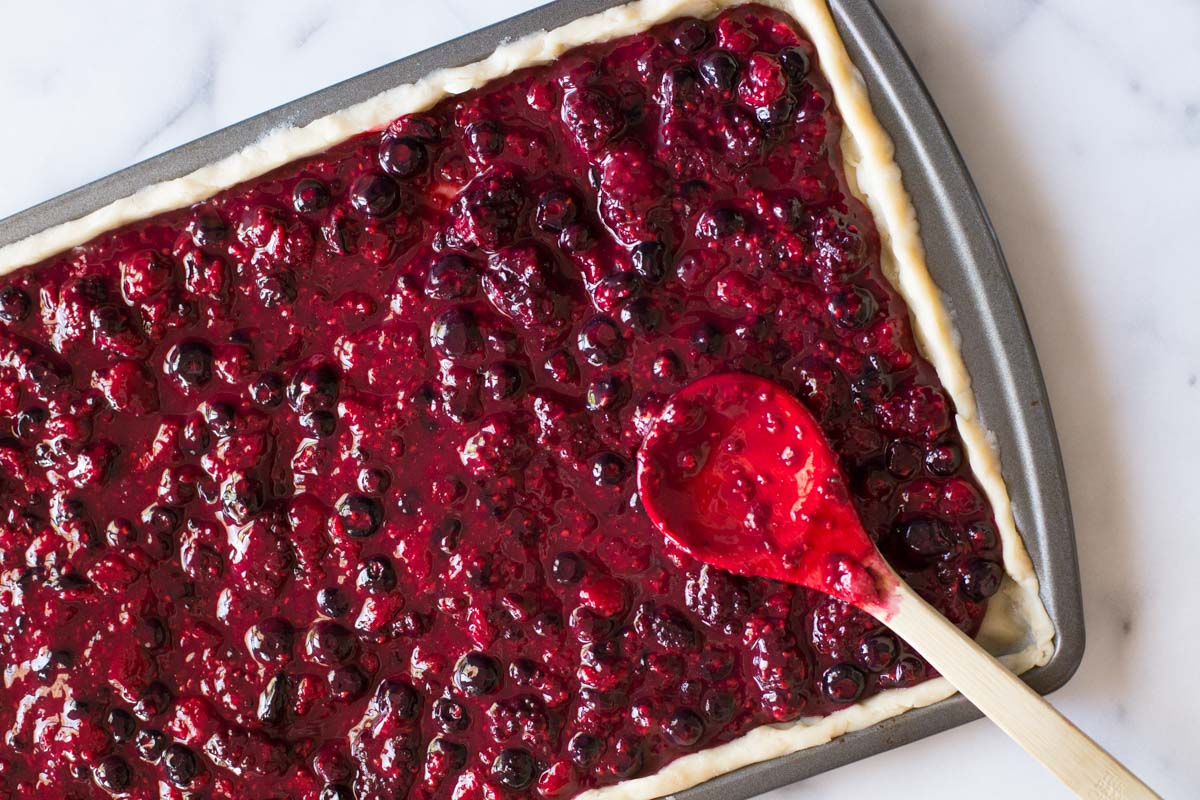 Triple Berry Slab filled with berry filling, ready to be topped with a top crust.