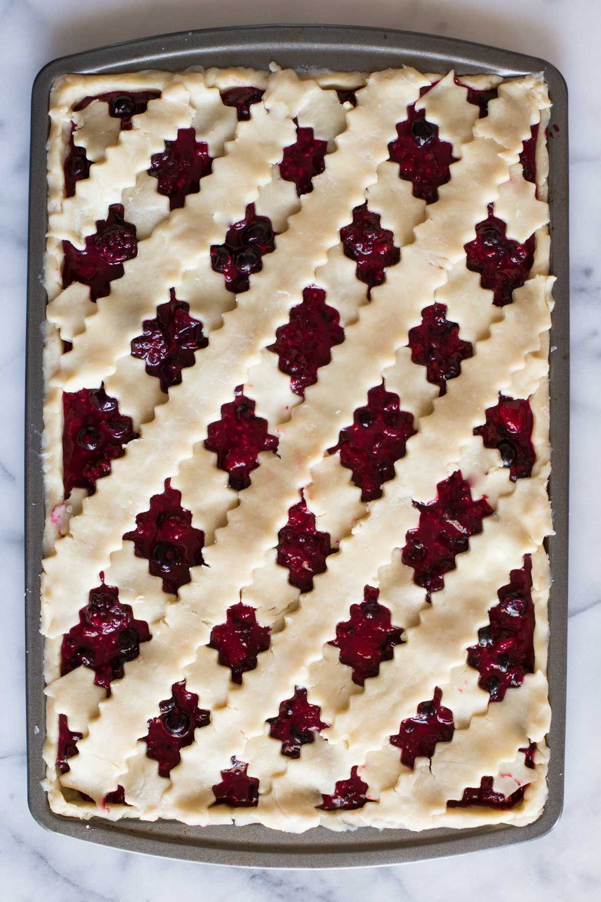 Triple Berry Slab Pie topped with a lattice crust ready to be baked.