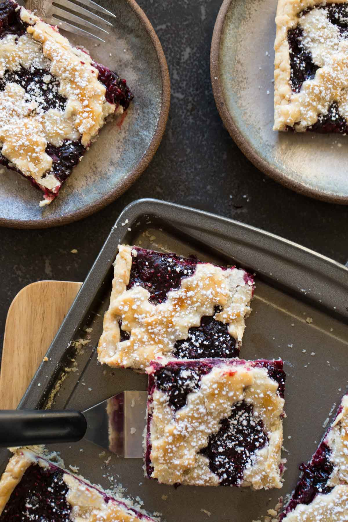 Triple Berry Slab Pie cut into squares and served on two dessert plates.