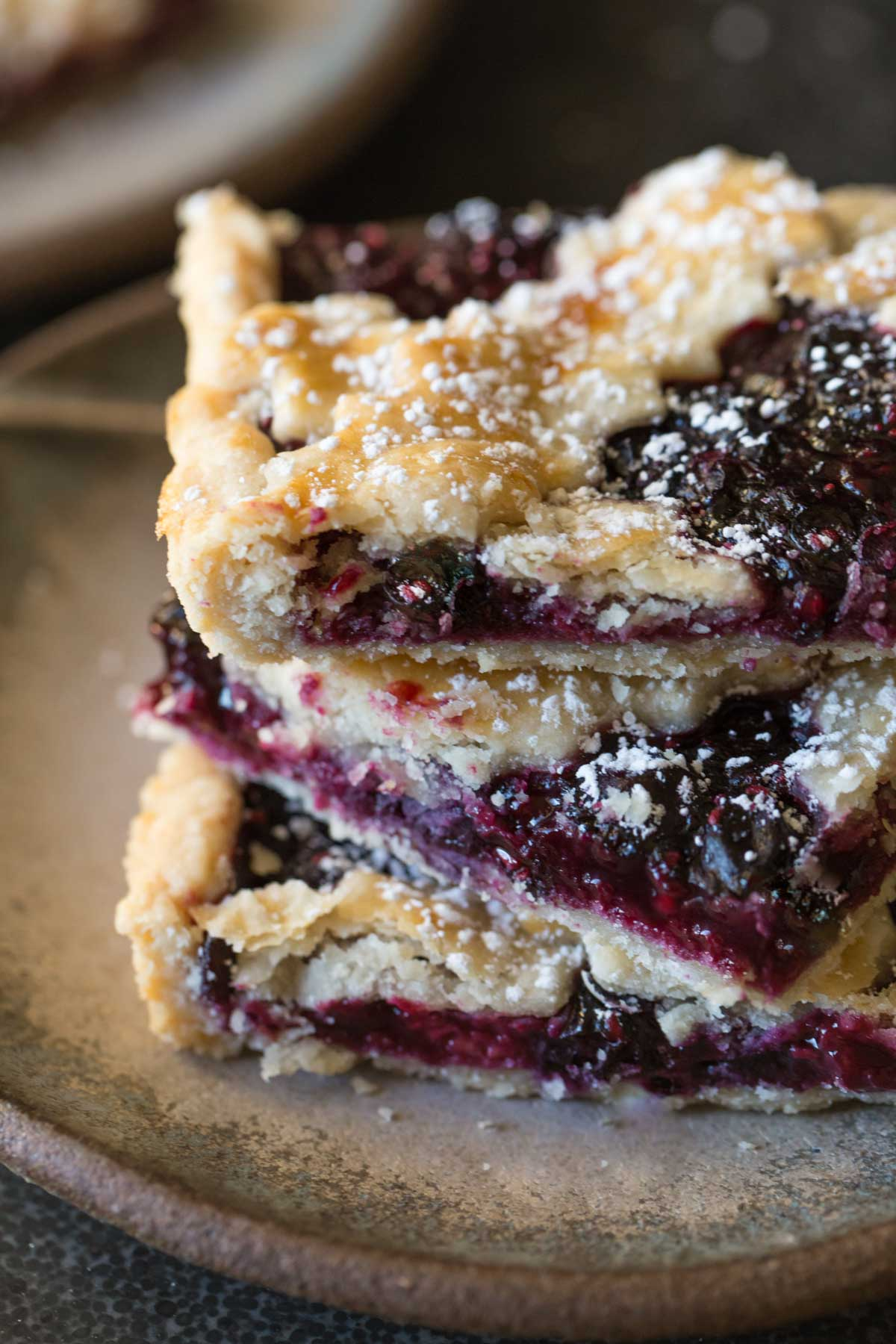 A close up of three pieces of Triple Berry Slab Pie stacked on a plate.