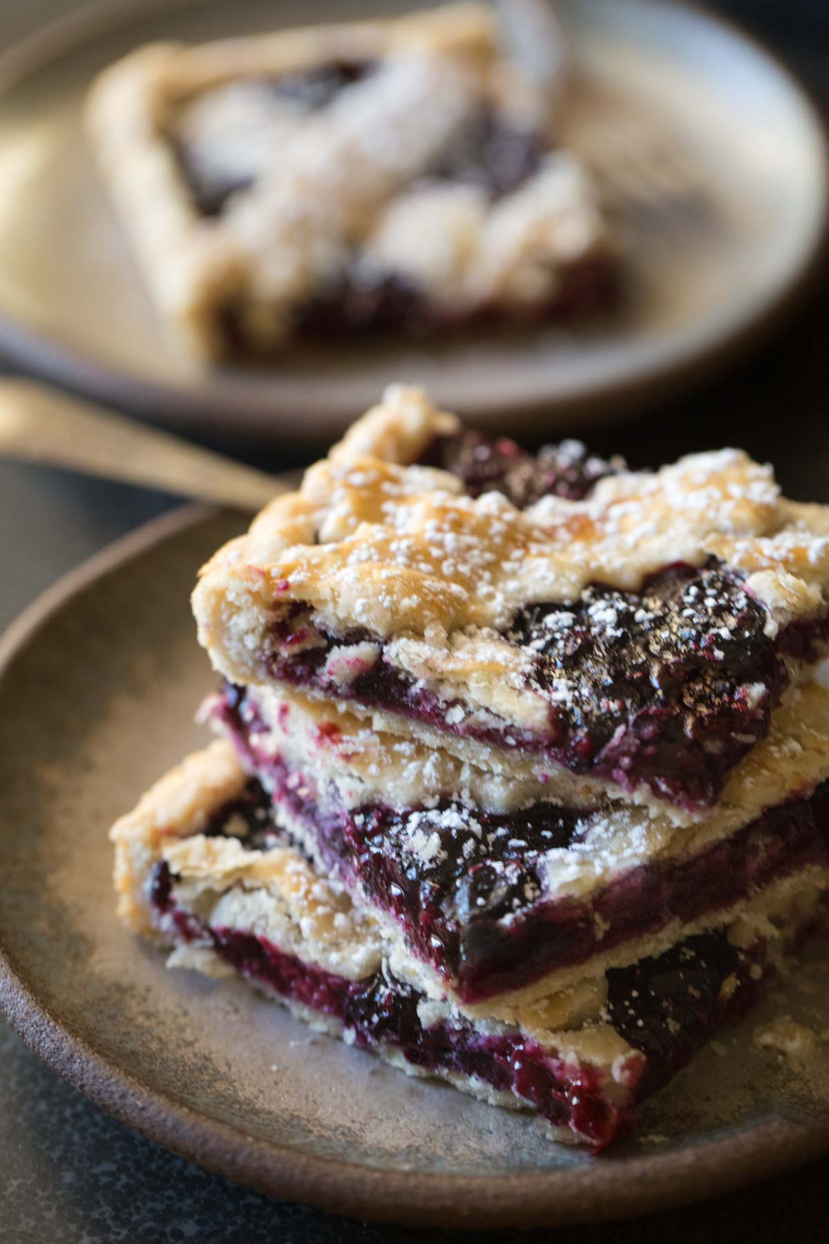 Three slices of Triple Berry Slab Pie stacked on a plate.
