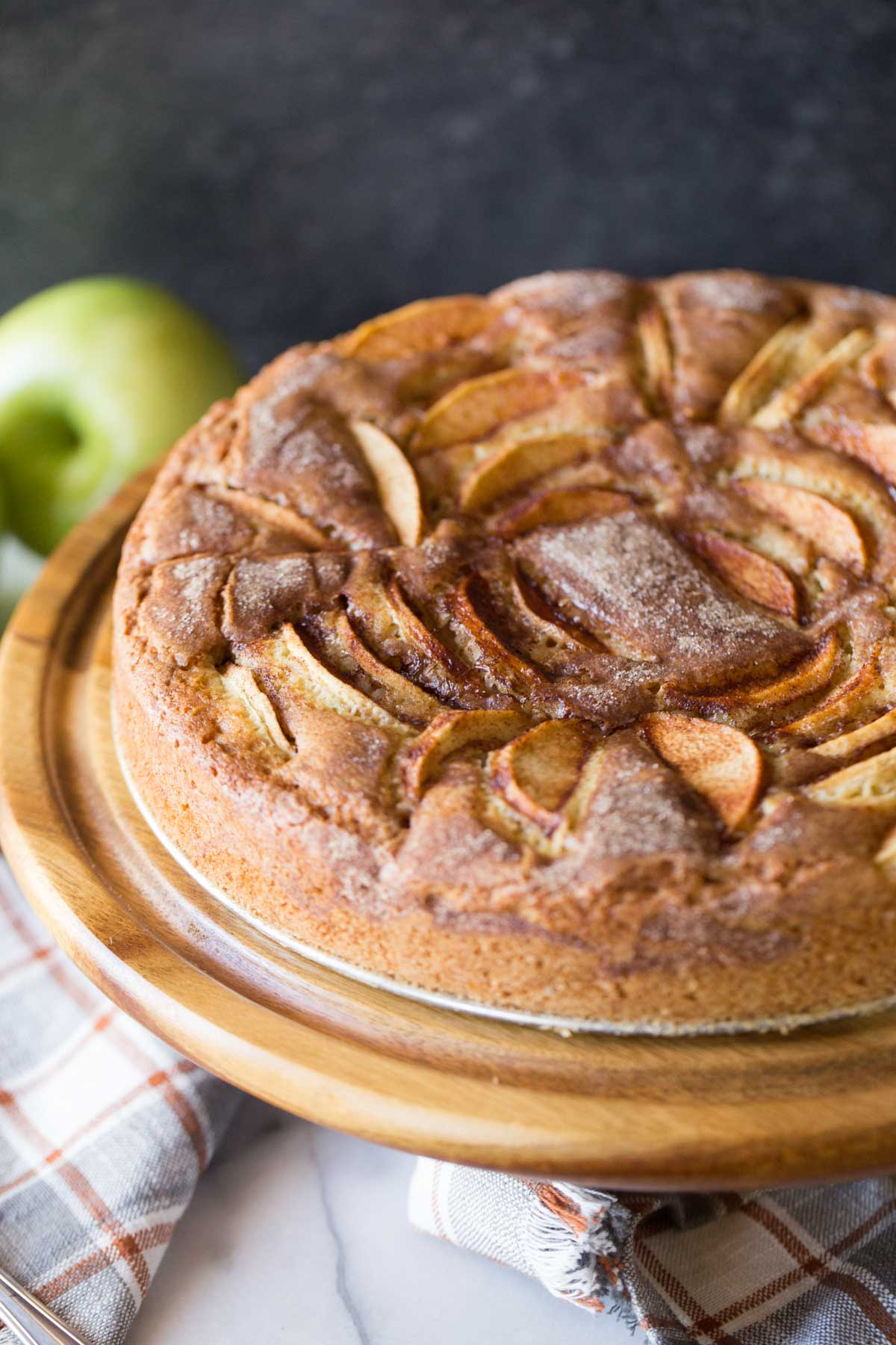 Apple Cider Cake from the front view on a wooden cake stand.