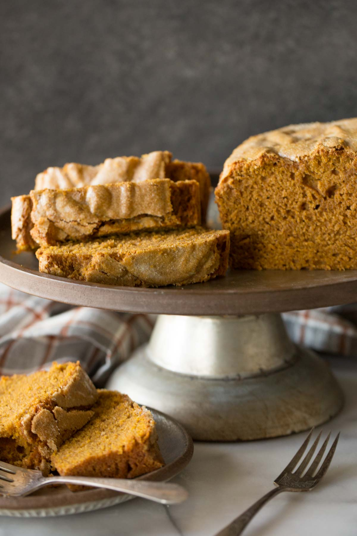 Slices of Easy Pumpkin Bread on a metal cake stand.