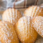 Close up view of Lemon Vanilla Madeleines with a dusting of powdered sugar.