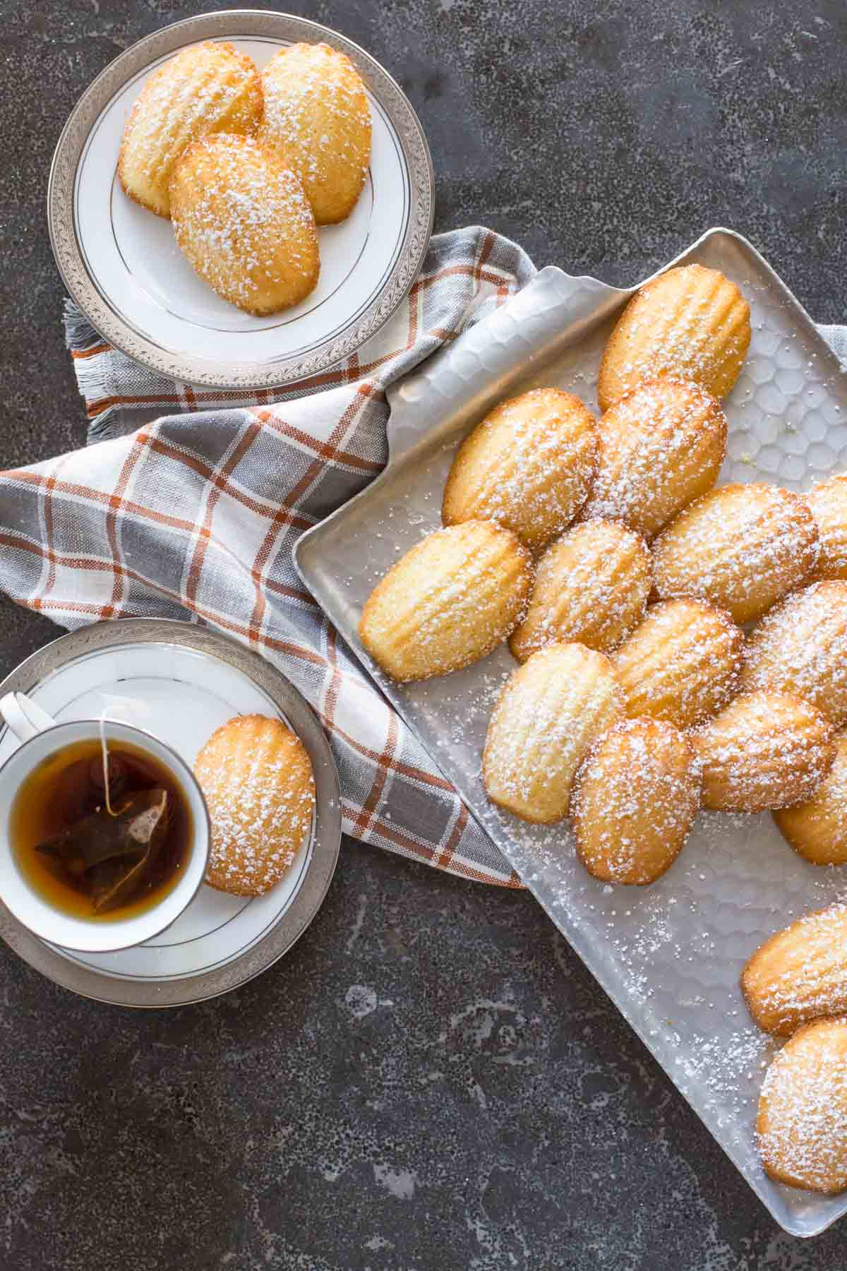 Overhead view of a platter of Lemon Vanilla Madeleines with a cup of tea.