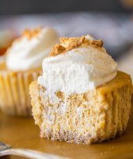 Close up shot of the inside of pumpkin spice cheesecakes topped with whipped cream