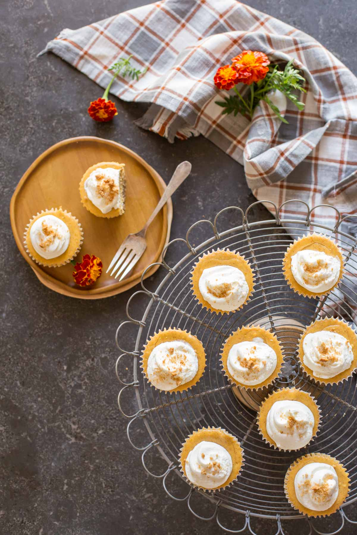 Top down view of Mini Pumpkin Spice Cheesecakes on a cake server and plate with whipped cream on top.