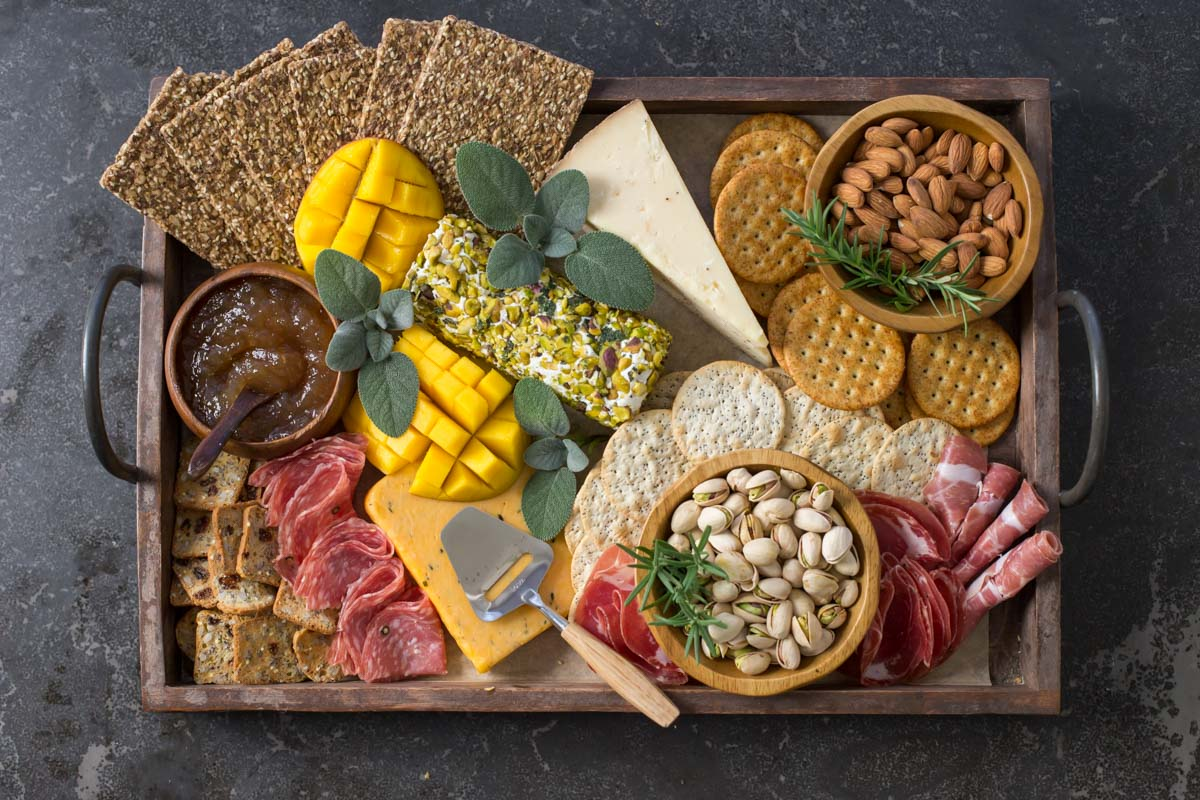 Overhead view of Pistachio Crusted Cheese Log displayed as part of a charcuterie.