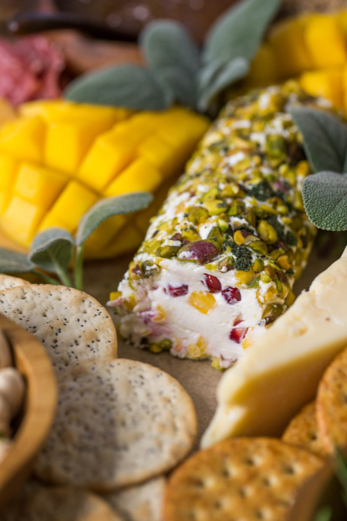 Close up view of Pistachio Crusted Cheese Log displayed as part of a charcuterie.