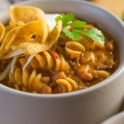 A close up shot of a grey bowl filled with Beef Chili Queso with pasta, Fritos, source cream, and cilantro.