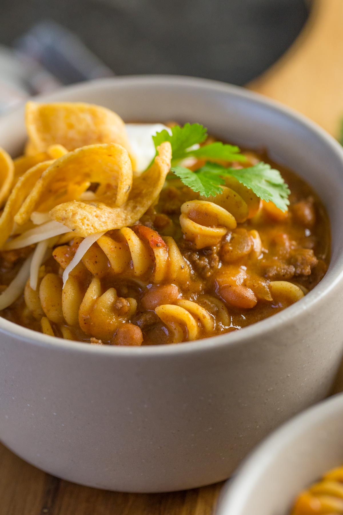 A close up shot of a grey bowl filled with Beef Queso Chili with pasta, Fritos, source cream, and cilantro.