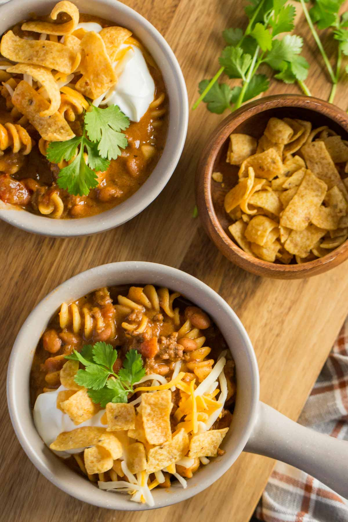 A top down view of two bowls Beef Queso Chili topped with sour cream, Fritos and Cilantro on a wooden board.
