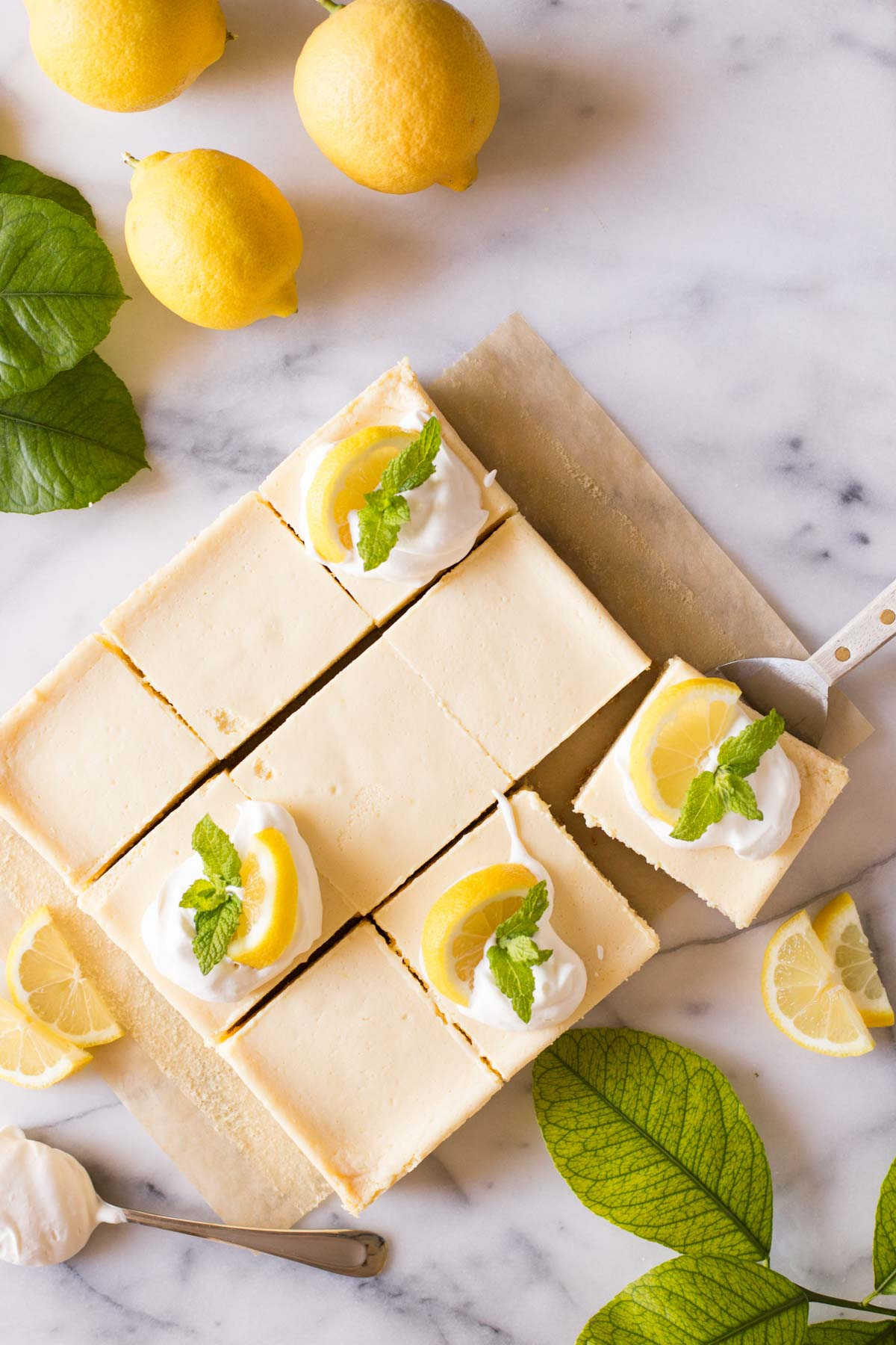 Overhead view of the Best Creamy Lemon Bars on a marble slab topped with lemon slices, fresh mint and whipped cream.