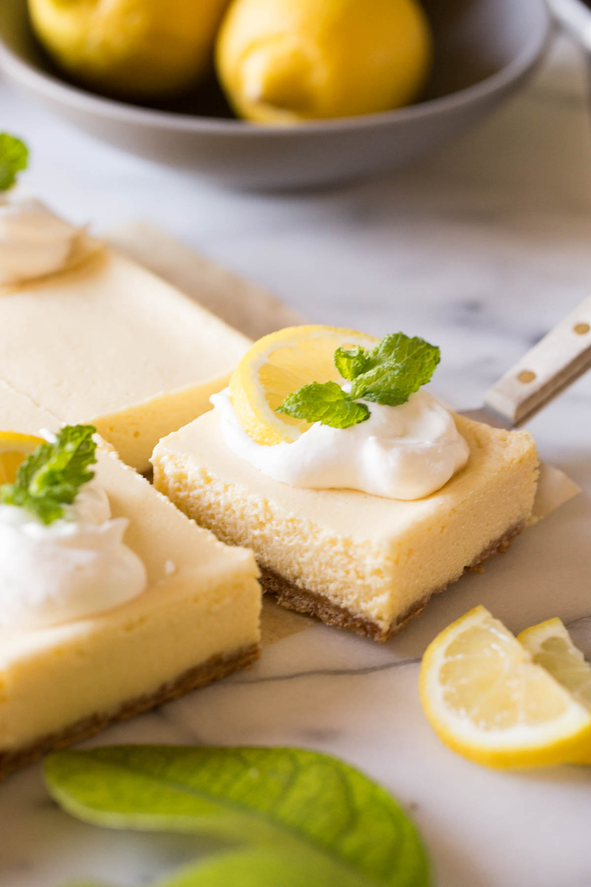 Close up view of Best Creamy Lemon Bar being lifted out of the pan with fresh lemons in the background.