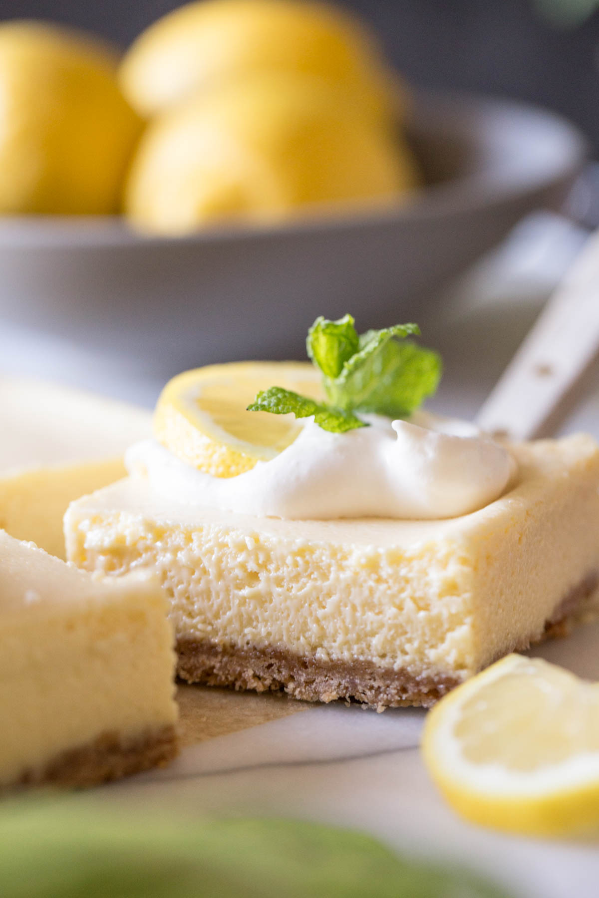 Close up view of the Best Creamy Lemon Bars on a marble slab topped with lemon slices, fresh mint and whipped cream.