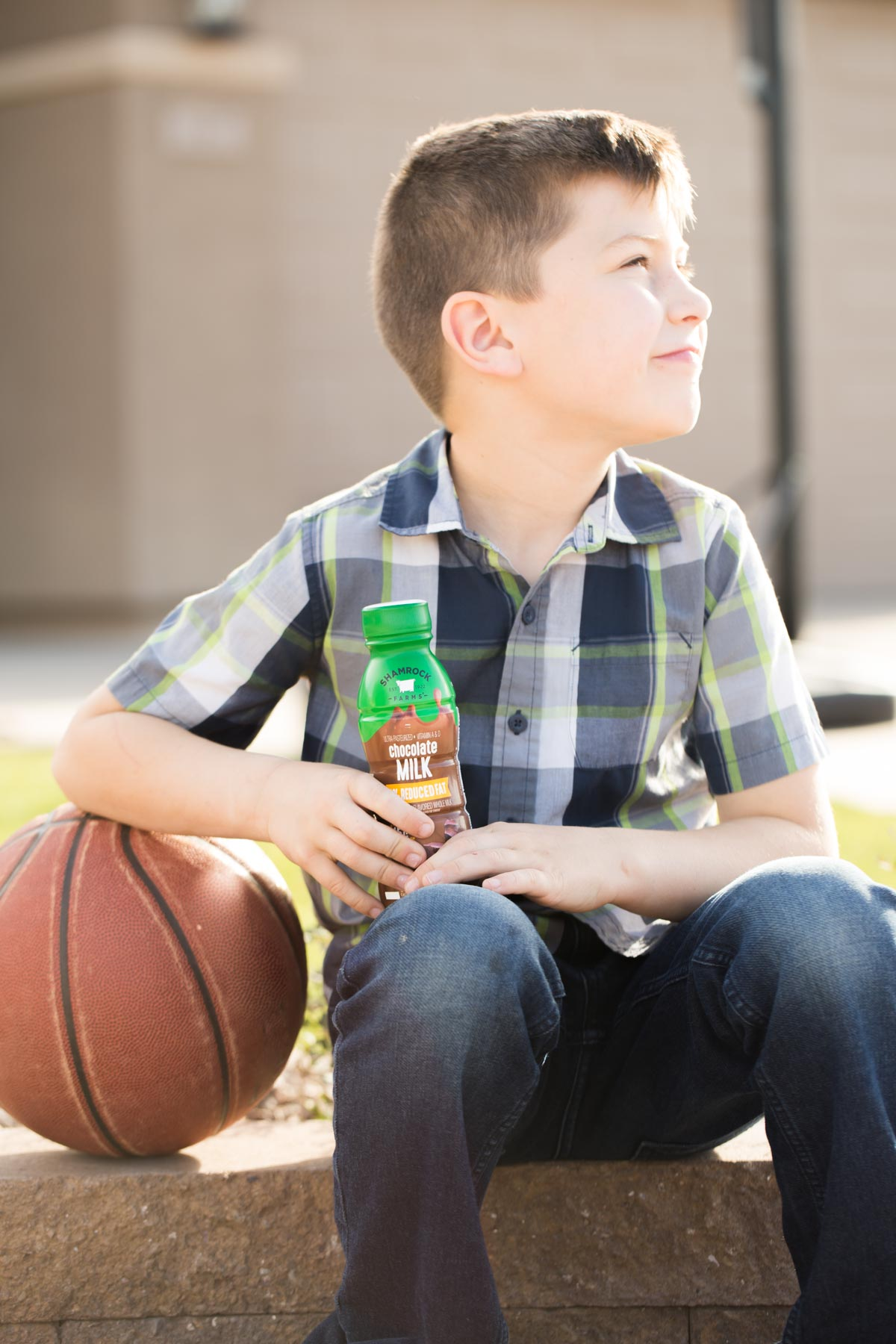 Boy sitting by a basketball with Shamrock Farms chocolate milk in his hand.