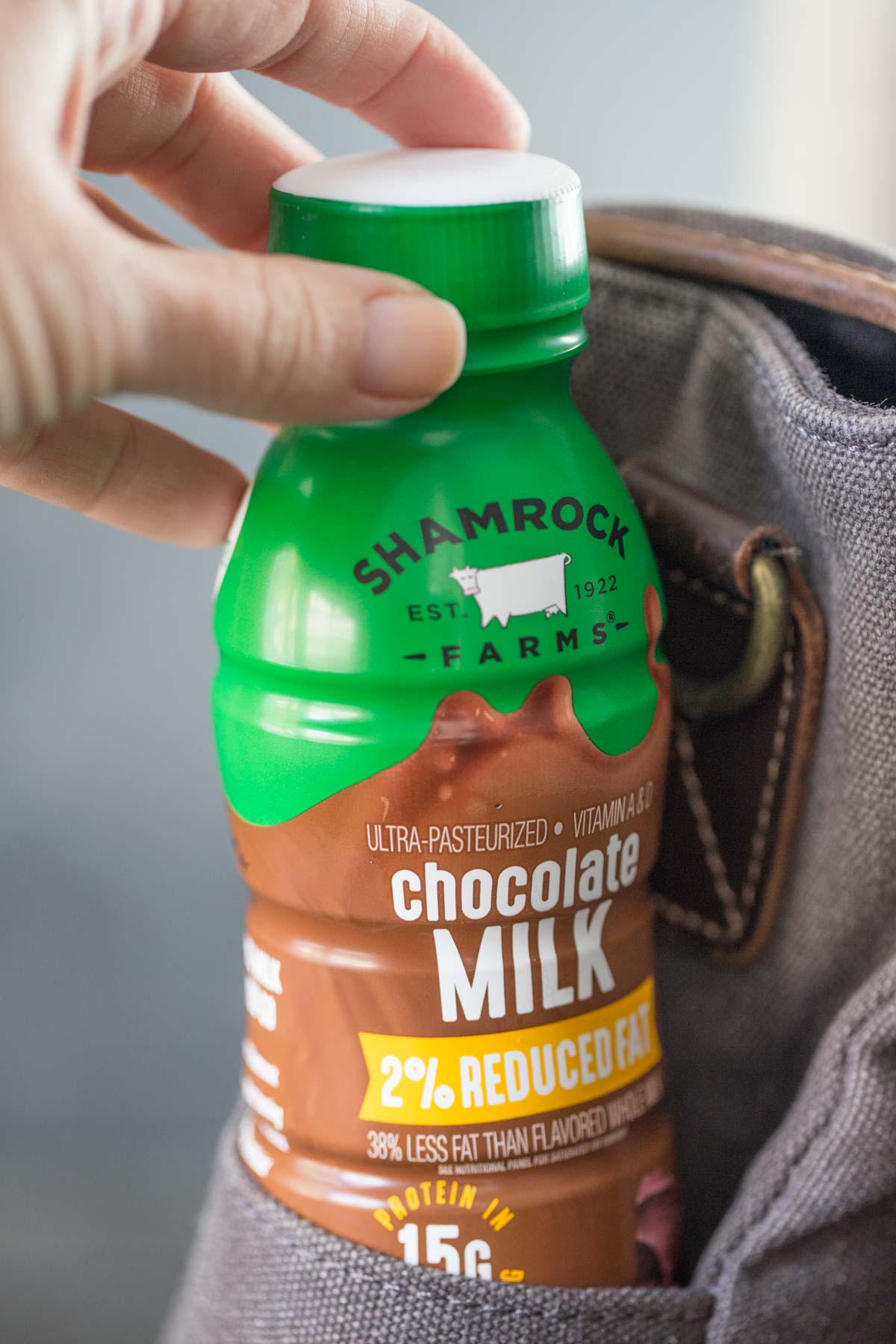 Close up of Shamrock Farms chocolate milk single serve size in the side pocket of a laptop bag.