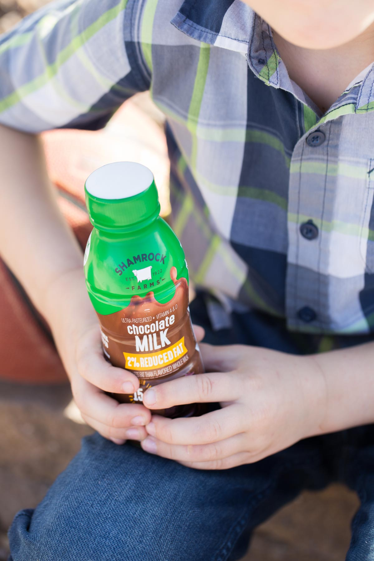 Close up of Shamrock Farms chocolate milk in his hand.