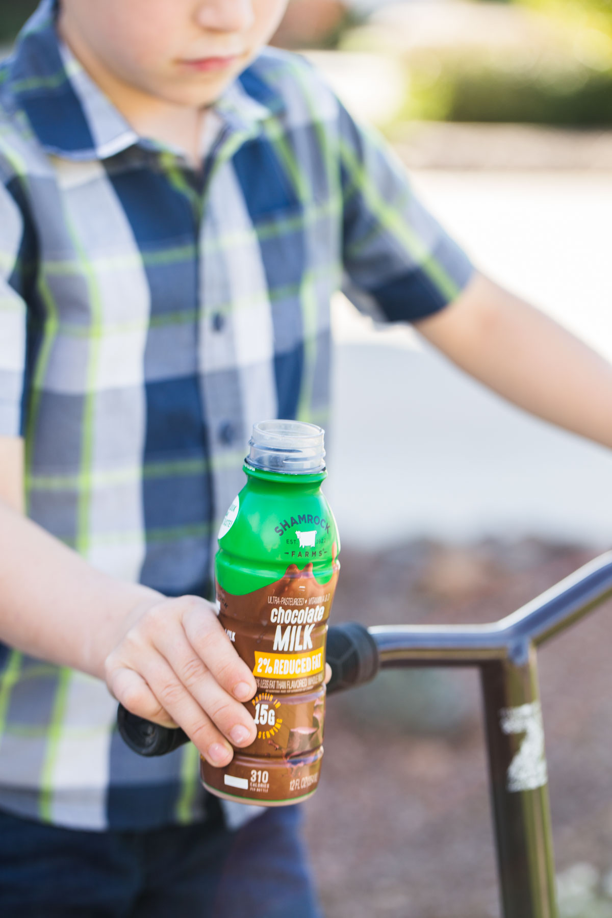 Boy riding a scooter with a single serve chocolate milk in one hand.