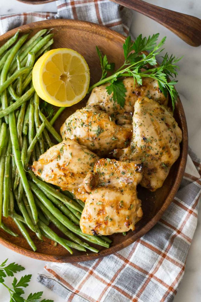 Overhead shot of Best Ever Chicken Marinade on a wooden platter with green beans and lemon.