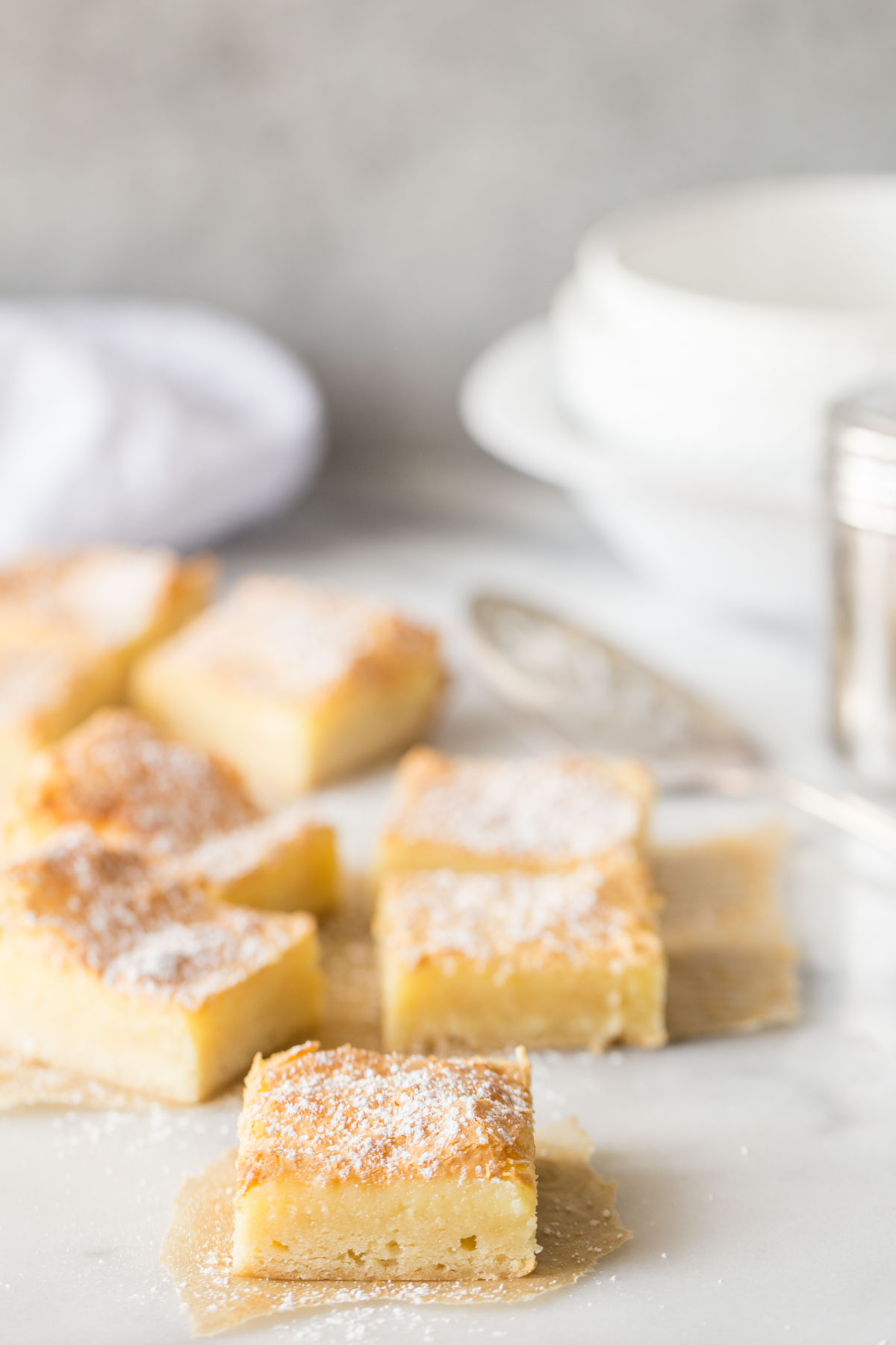 Gooey Butter Bars without cake mix cut into bars on a white marble background.