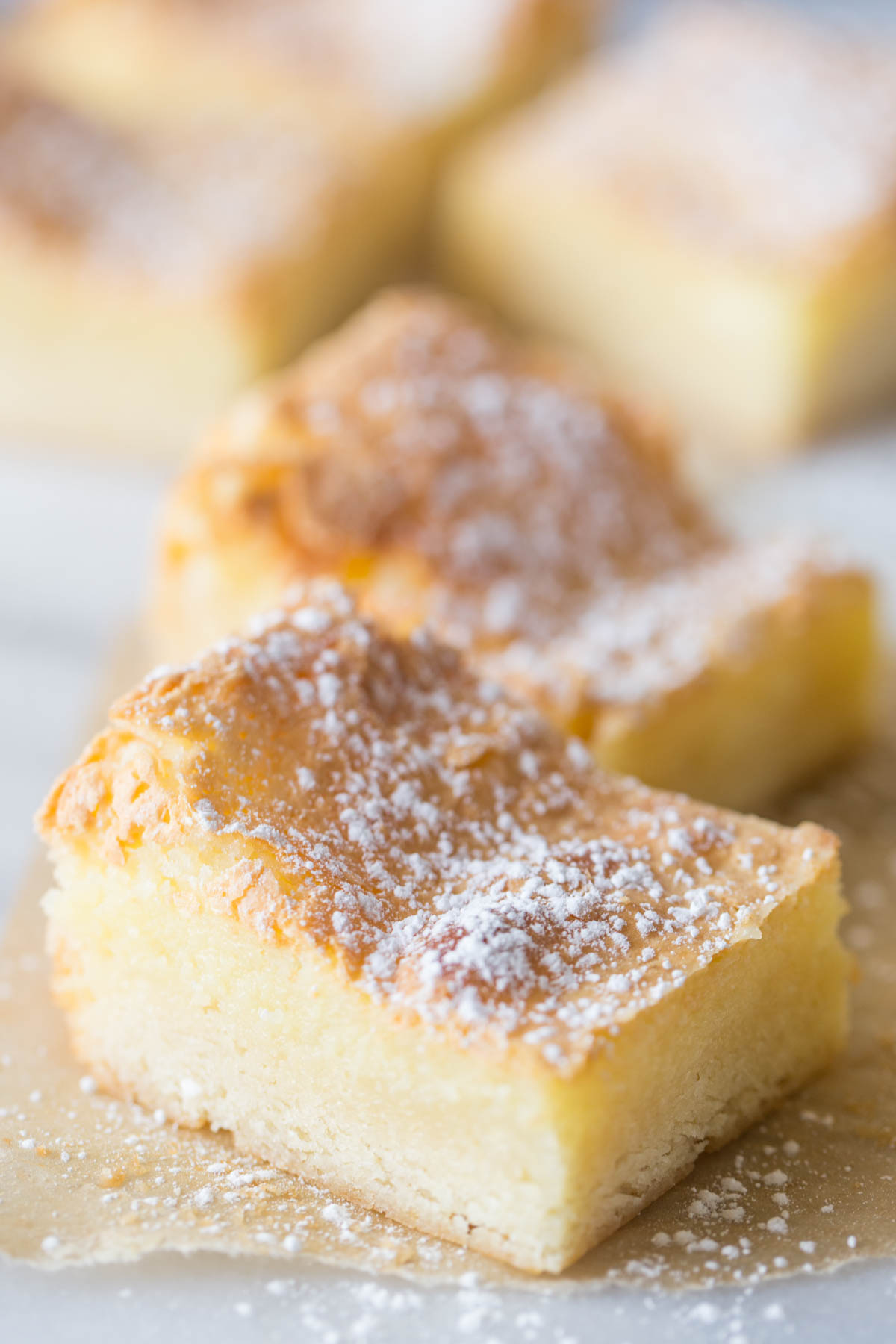 Close up view of Gooey Butter Bars on a white background.