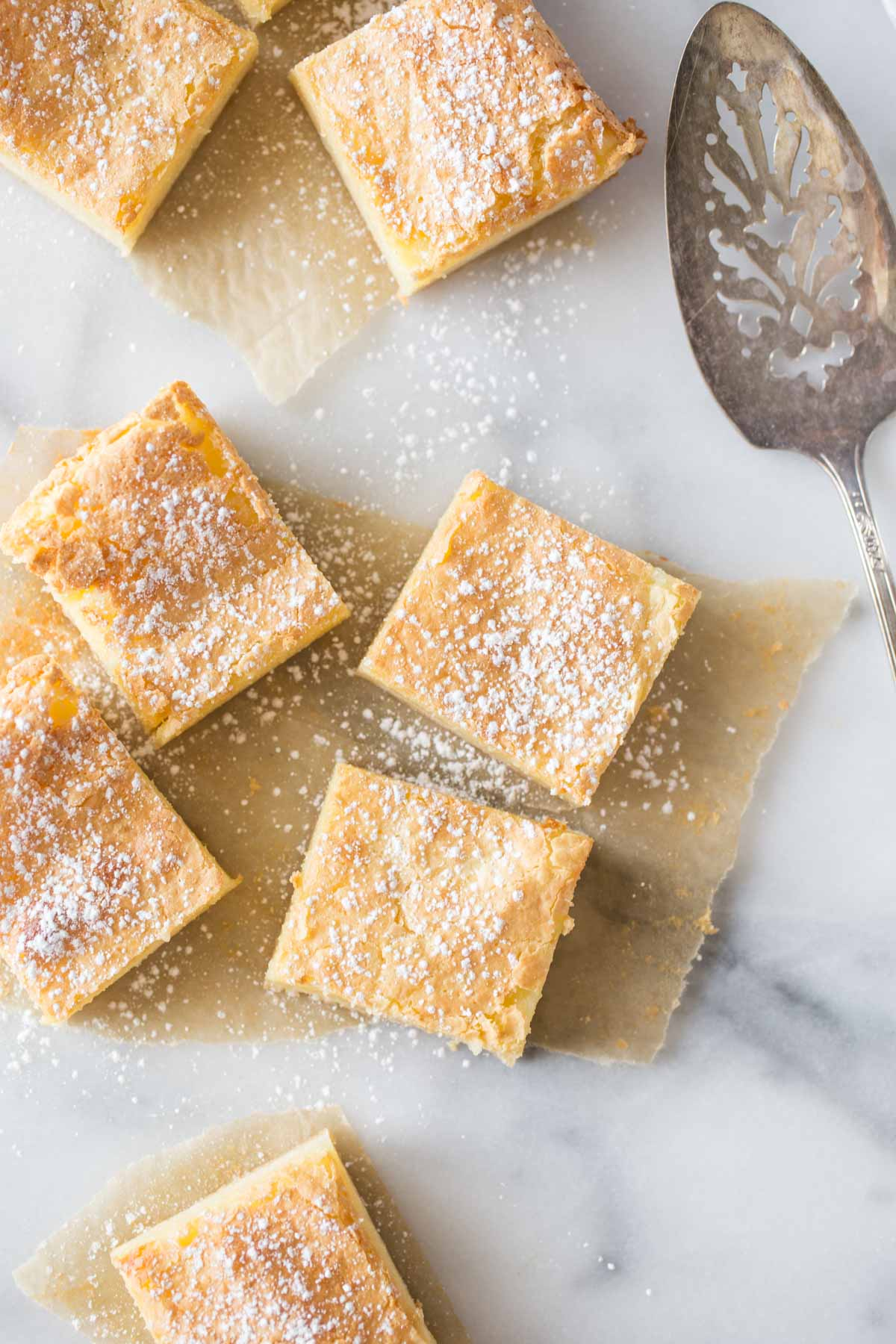 Overhead view of Gooey Butter Bars without cake mix cut into squares on a marble background.