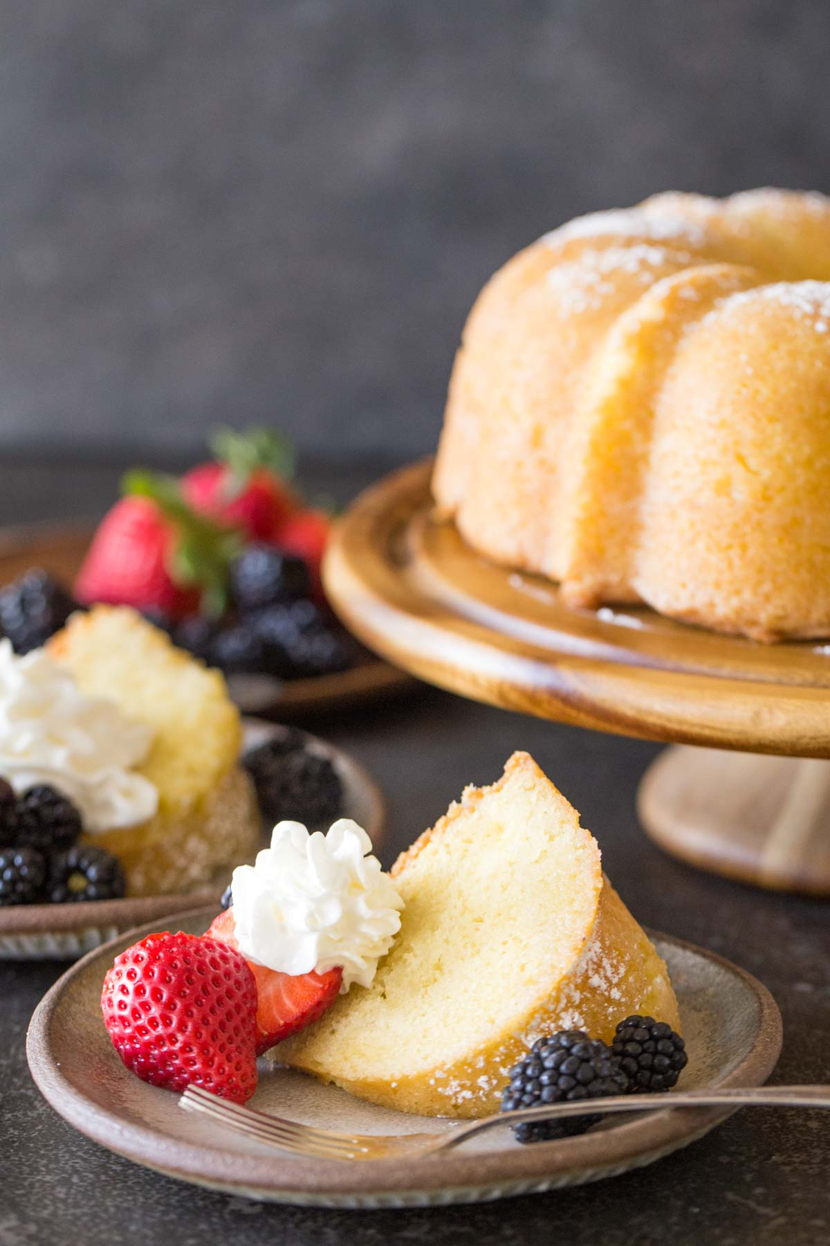 Kentucky Butter Cake on wooden cake stand with whipped cream and berries on a grey background.
