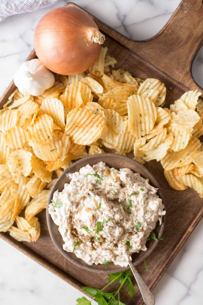 Overhead shot of Bowl of Roasted Garlic and Caramelized Onion Dip on a platter with chips.