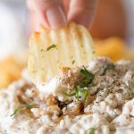 Chip dipping into bowl of Roasted Onion and Caramelized Onion Dip.