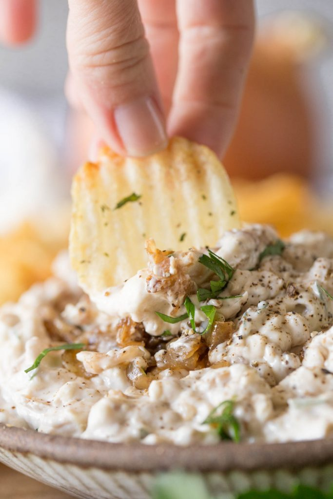 Chip dipping into Bowl of Roasted Garlic and Caramelized Onion Dip on a platter with chips.
