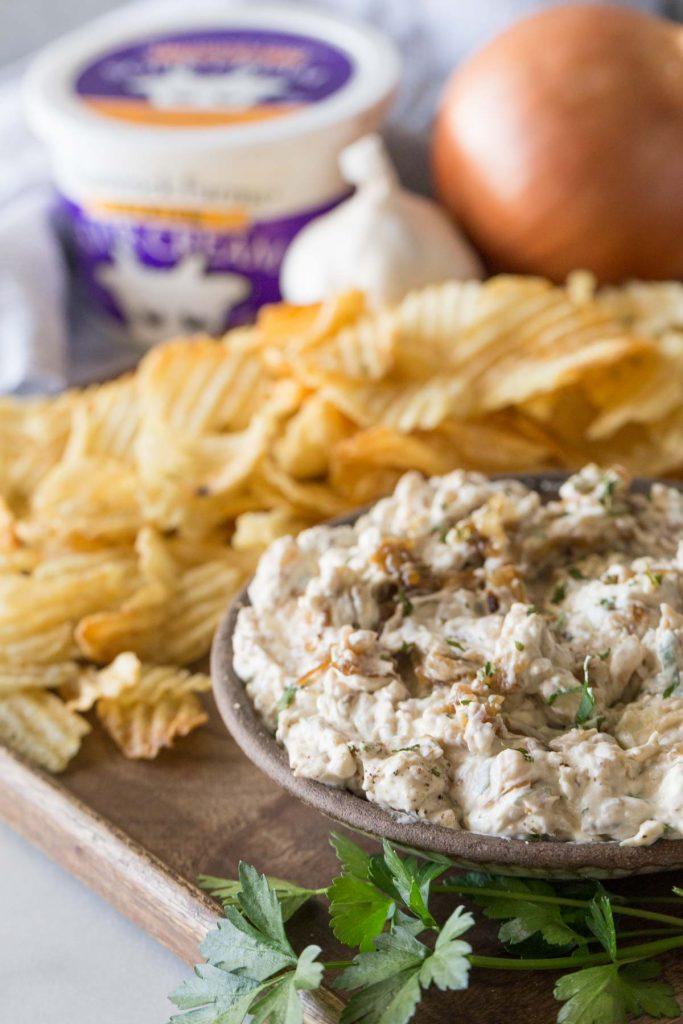 Bowl of Roasted Garlic and Caramelized Onion Dip on a platter with chips.