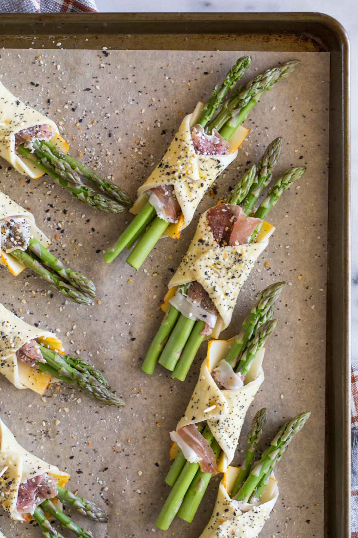 Overhead view of uncooked Puff Pastry Asparagus Bundles on a baking sheet.