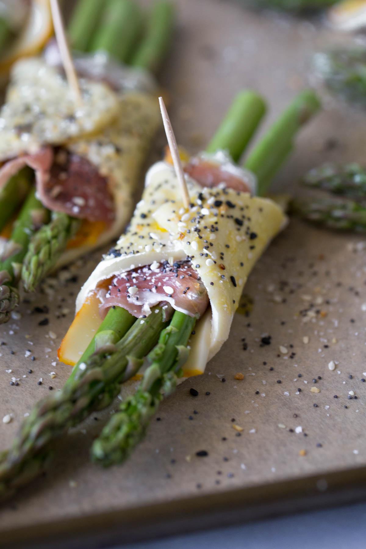 Close up view of uncooked asparagus bundles on parchment paper.