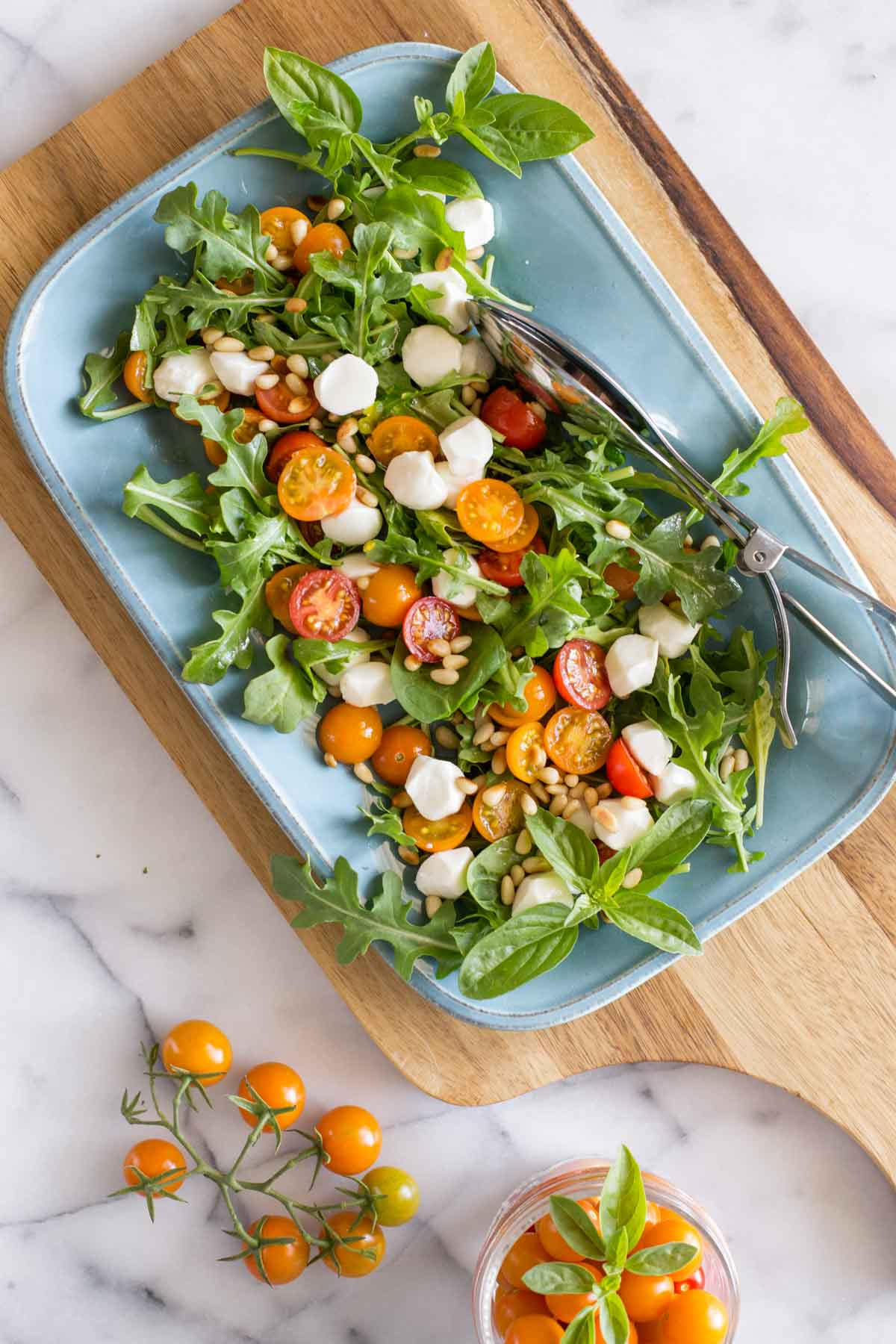 Overhead view of Sungold Caprese Salad on a blue platter.