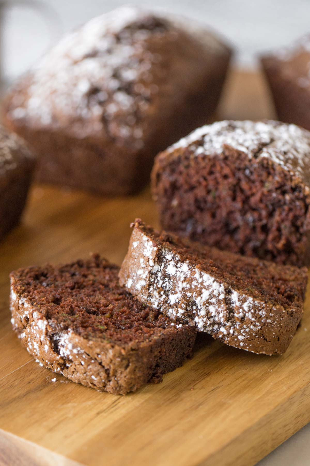 Slices of Chocolate Zucchini Bread on a wooden cutting board.