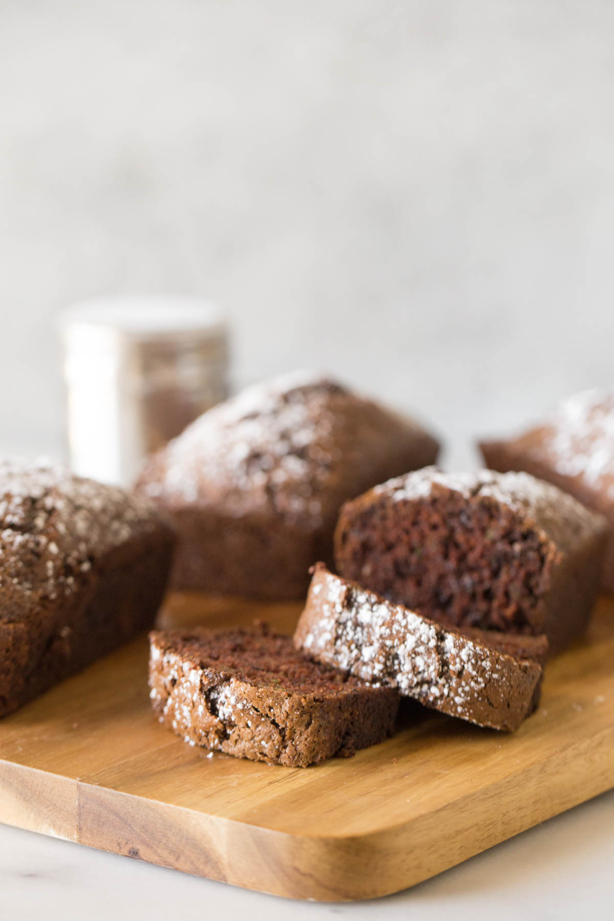 Loaves of Chocolate Zucchini Bread arranged on a wooden cutting board with a white background.