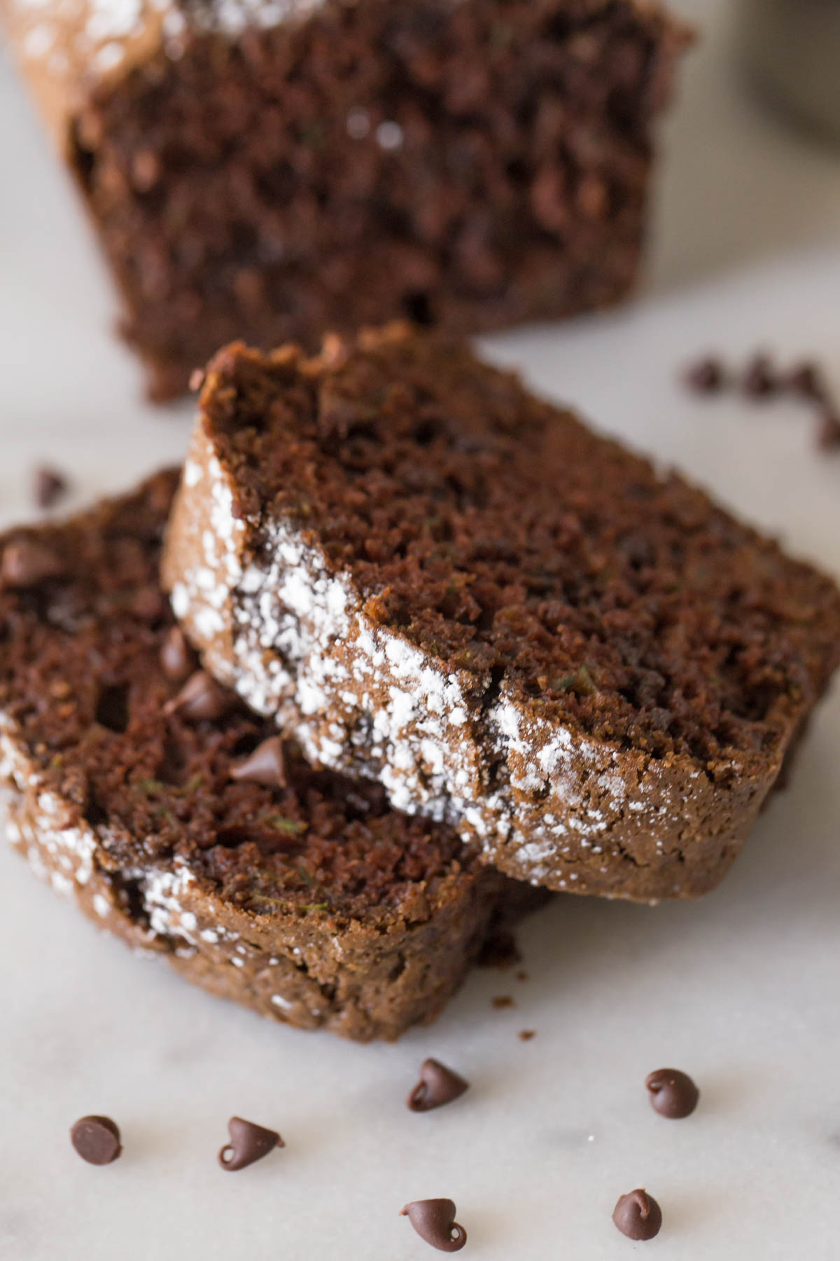 Close up view of slices of Chocolate Zucchini Bread on a marble background.
