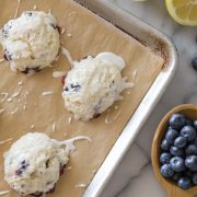 Glazed Lemon Blueberry Muffin Tops on a baking sheet with a grey background.