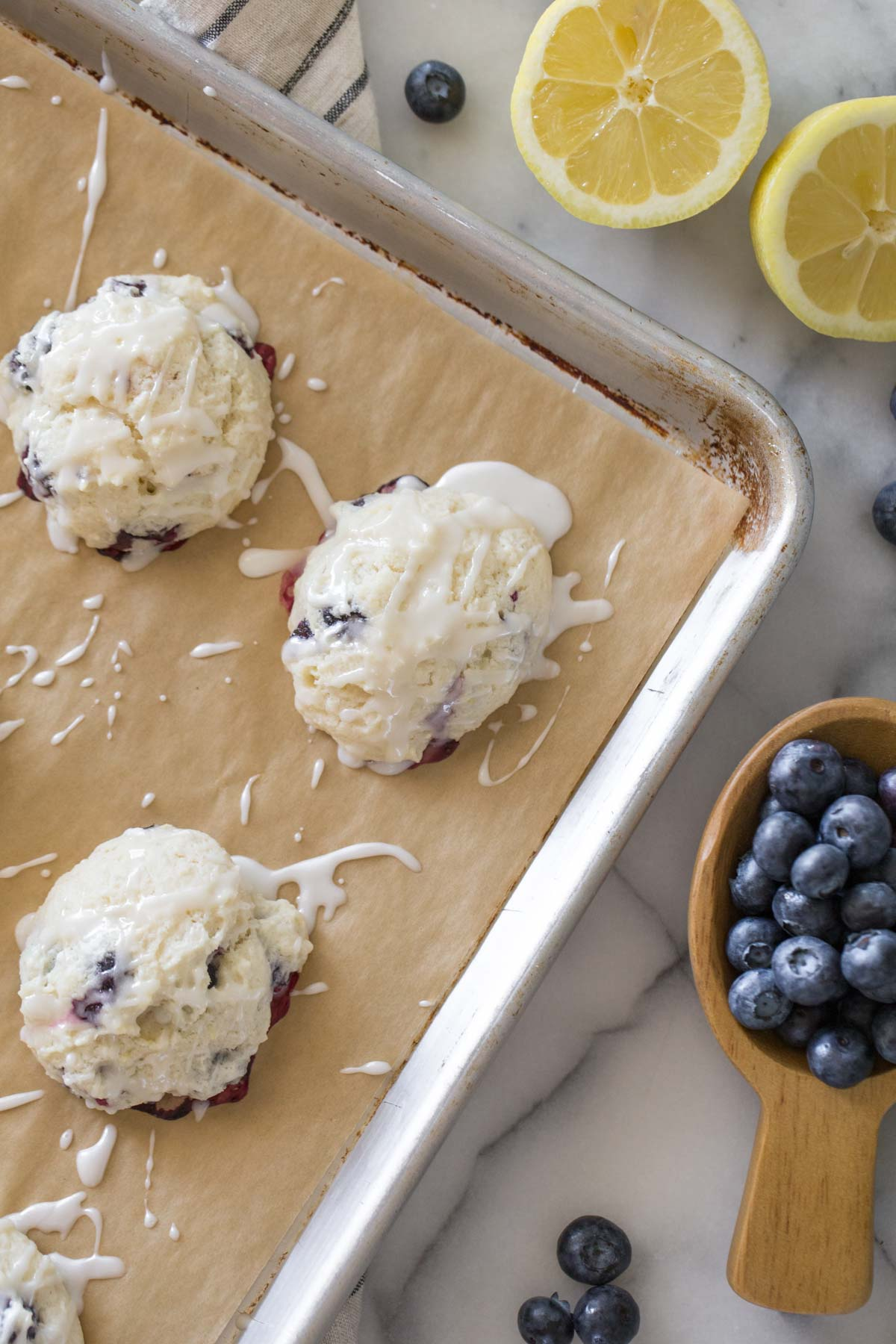 Glazed Lemon Blueberry Muffin Tops on a baking sheet with a grey background with fresh lemons and blueberries.