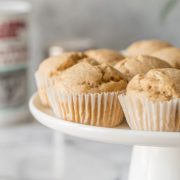 One Bowl Applesauce Muffins sitting on a white cake stand with a grey background.