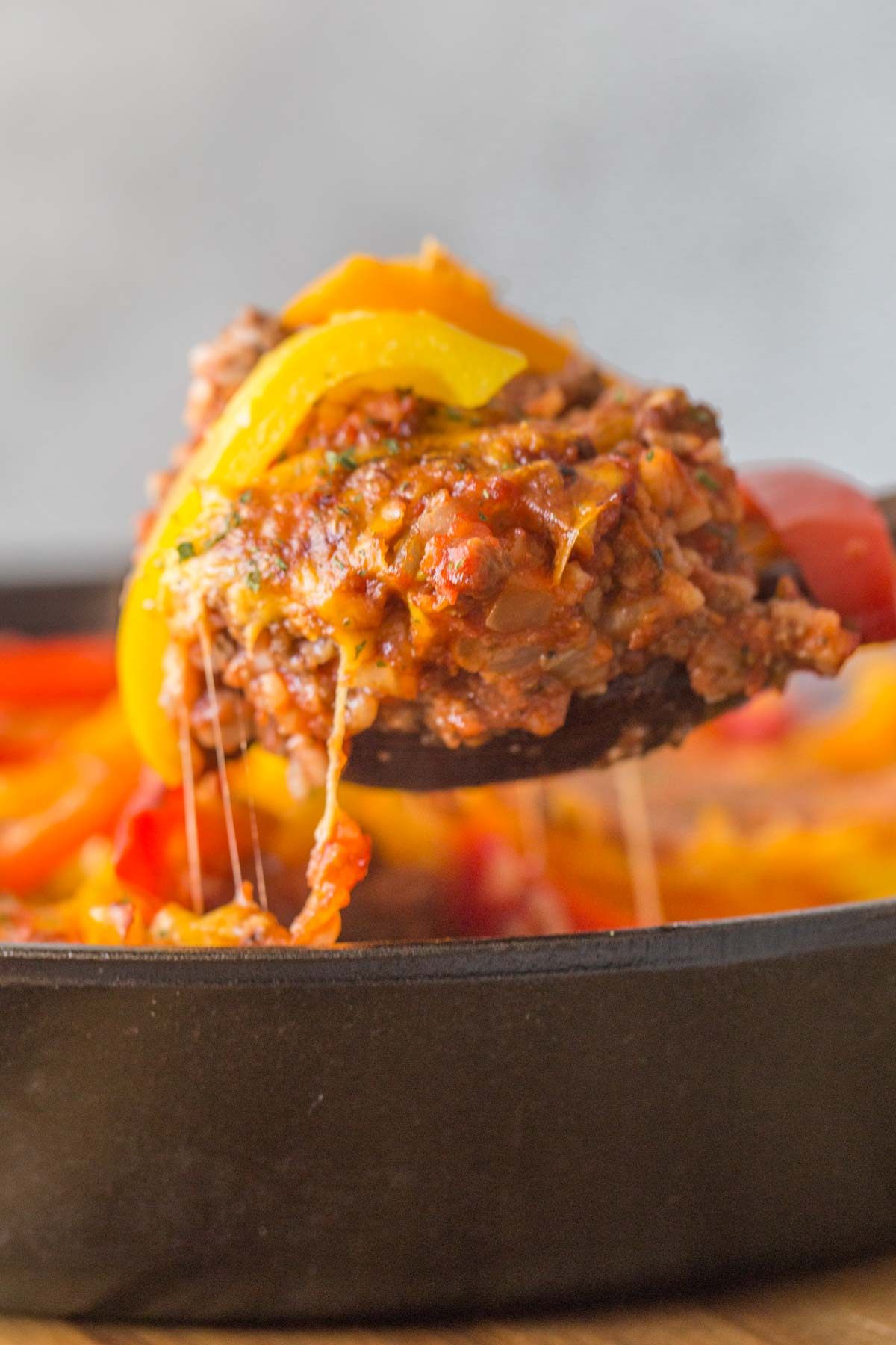 Close up shot of Unstuffed Pepper Skillet being served out of the skillet with melty cheese.