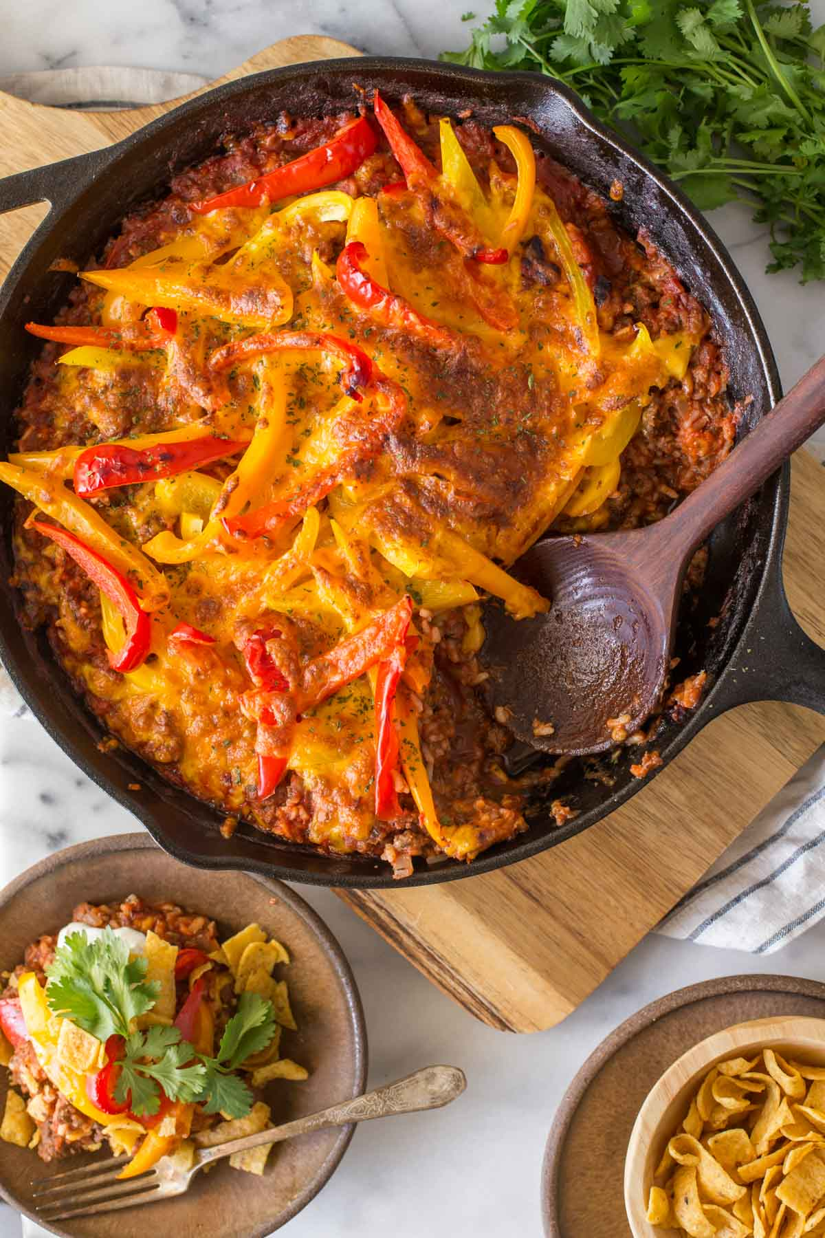 Overhead view of Unstuffed Pepper Skillet on a white marble board with a wooden serving spoon.
