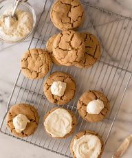 Bakery Style Molasses Cookies on a white marble board in the process of frosting.