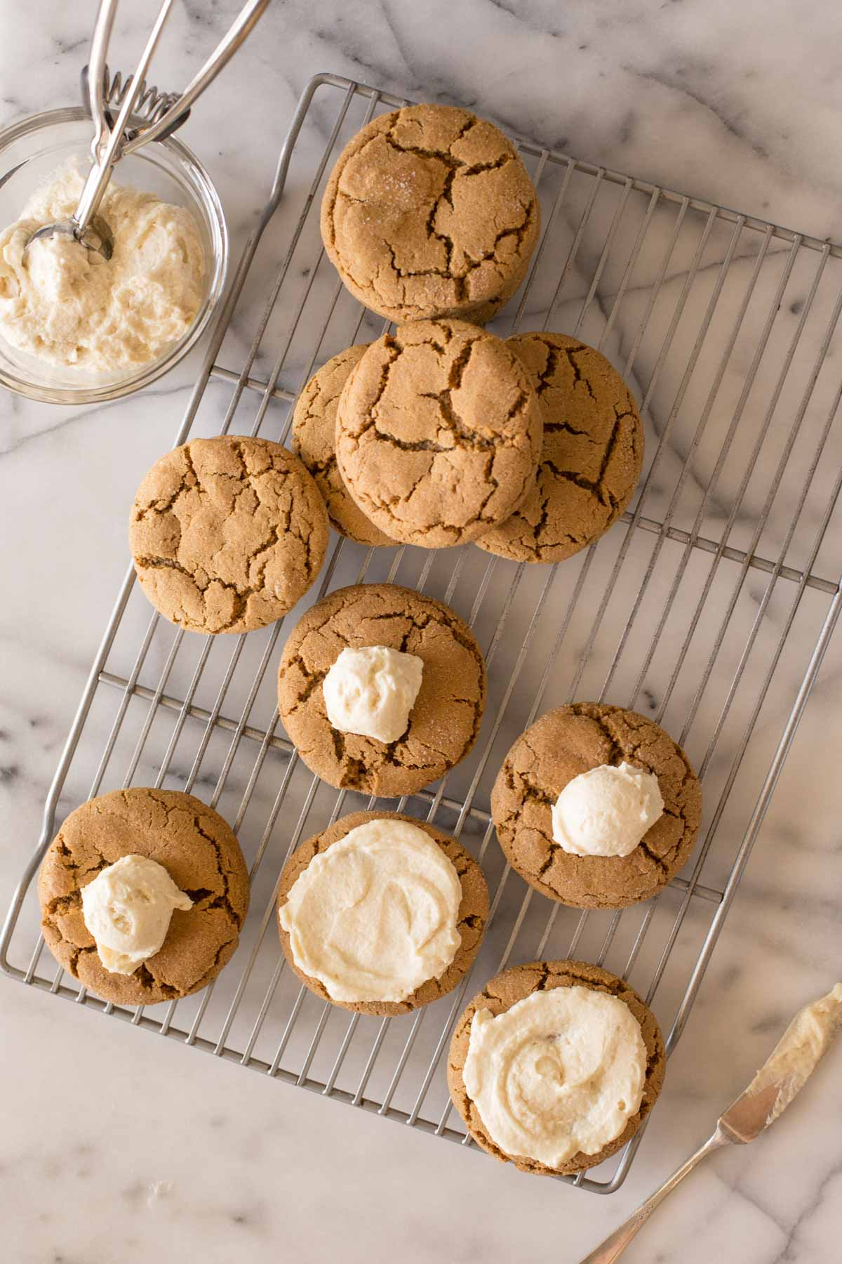 Overhead view of Bakery Style Molasses Cookies on a white marble board in the process of being frosted.