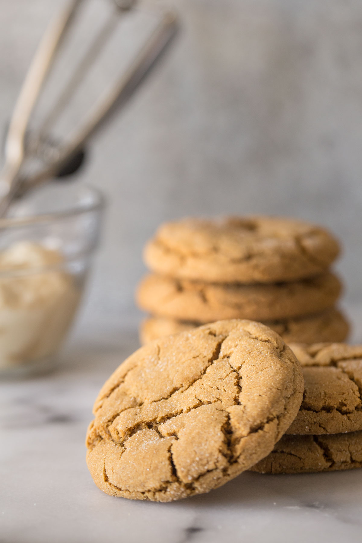 Bakery Style Molasses Cookies stacked on a white marble board.