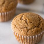 Close up view of the top of a Cinnamon Applesauce Muffin on a white background.